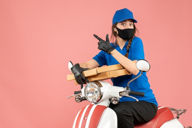 Bovenaanzicht van een verraste vrouwelijke koerier met een medisch masker en handschoenen die op een scooter zitten en bestellingen afleveren die op pastel perzik wijzen