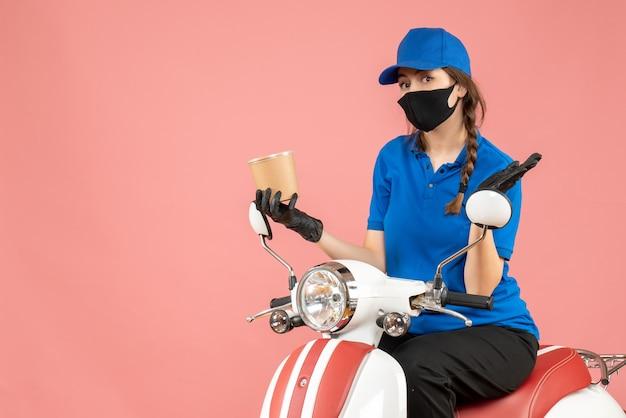 Bovenaanzicht van een verraste vrouwelijke koerier met een medisch masker en handschoenen die op een scooter zitten en bestellingen afleveren op pastel perzik