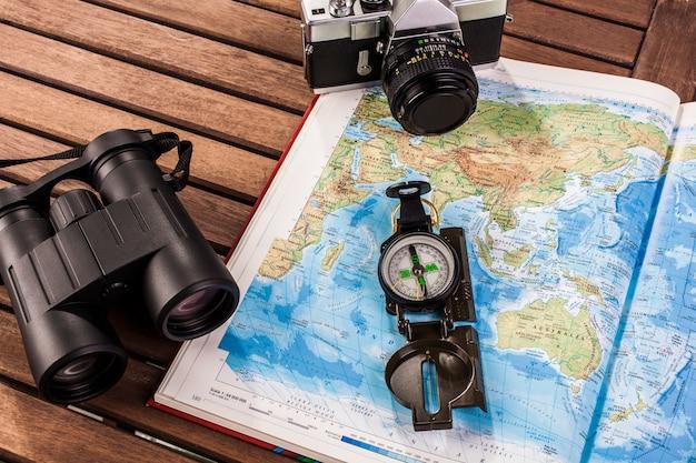 Bovenaanzicht van een verrekijker, kompas, fotocamera en kaart