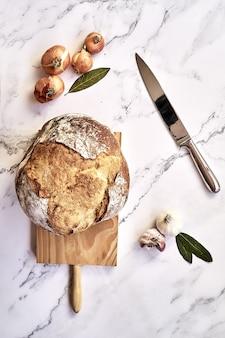 Bovenaanzicht van een vers gebakken traditioneel brood op een houten bord met uien, knoflook en een mes