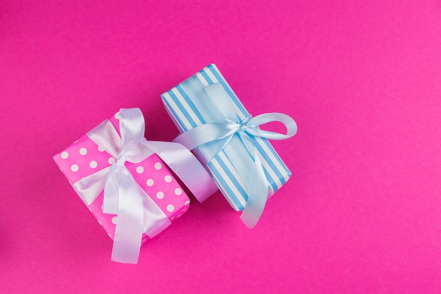 Bovenaanzicht van een versierd heden met een strik op roze achtergrond