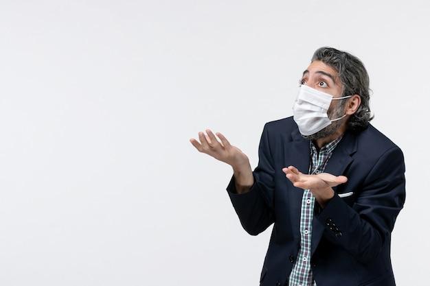 Bovenaanzicht van een verwarde jonge kerel in pak die een masker draagt en omhoog kijkt op een witte achtergrond