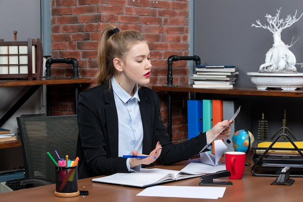 Bovenaanzicht van een verwarde jonge vrouw die aan een tafel zit en een document leest op kantoor