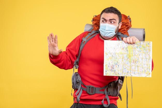 Bovenaanzicht van een verwarde reiziger die een medisch masker draagt met een rugzak met een kaart met vijf op een gele achtergrond