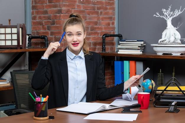 Bovenaanzicht van een verwarde vrouw die aan een tafel zit en een blauwe documentpen vasthoudt op kantoor