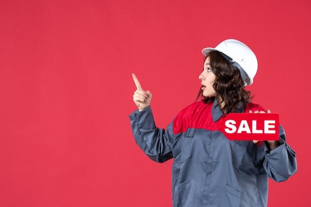 Bovenaanzicht van een verwarde vrouwelijke bouwer in uniform met een helm en een verkooppictogram dat aan de rechterkant op geïsoleerde rode achtergrond omhoog wijst
