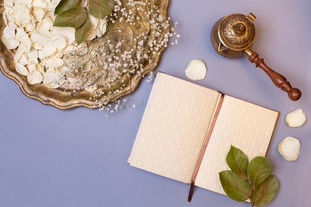 Bovenaanzicht van een vintage dienblad met witte droge rozenblaadjes, cezve en dagboek op een blauwe achtergrond. plat leggen, plaats voor tekst.