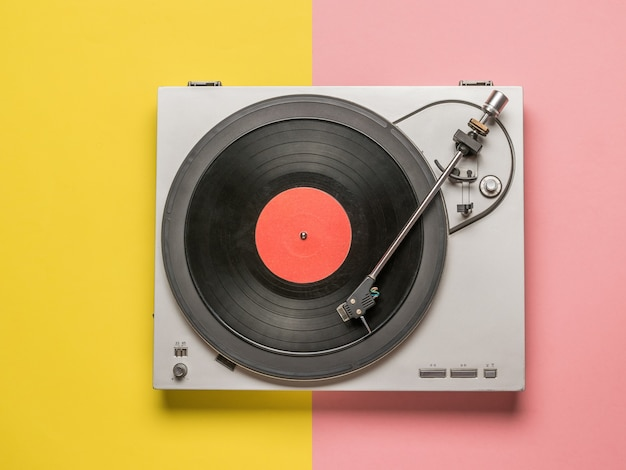 Bovenaanzicht van een vinyl platenspeler op een rood en geel oppervlak