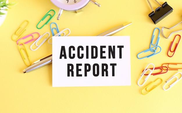 Bovenaanzicht van een visitekaartje met tekst accident report, pen, paperclips en klok op een geel oppervlak.