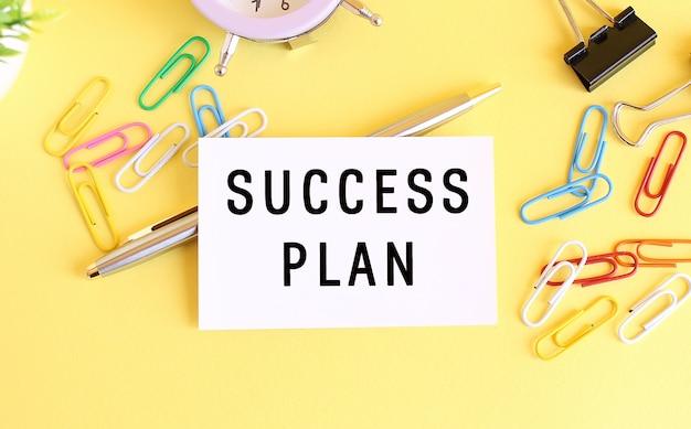 Bovenaanzicht van een visitekaartje met tekst success plan op een gele achtergrond