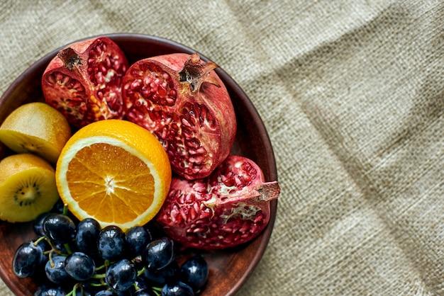 Bovenaanzicht van een vol bord met sappig gesneden fruit op een houten bord
