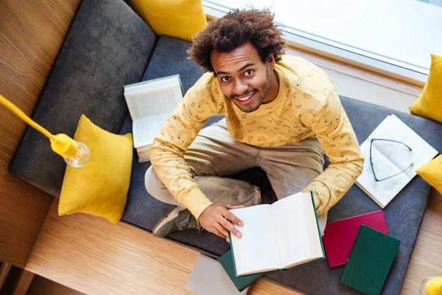 Bovenaanzicht van een vrolijke afro-amerikaanse jongeman die een boek leest en thuis glimlacht