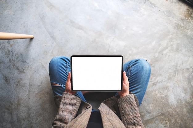 Bovenaanzicht van een vrouw die en tablet-pc met lege witte desktop scherm gebruikt terwijl zittend op de vloer