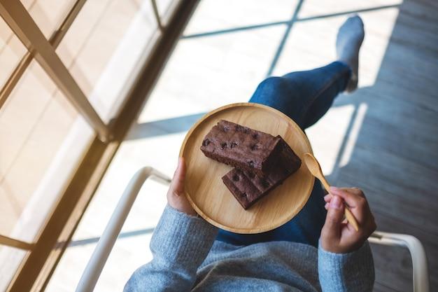 Bovenaanzicht van een vrouw die heerlijke browniecake met lepel vasthoudt en eet