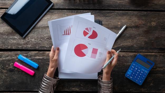 Bovenaanzicht van een vrouw die rapporten en papierwerk leest vol statistische grafieken en diagrammen.