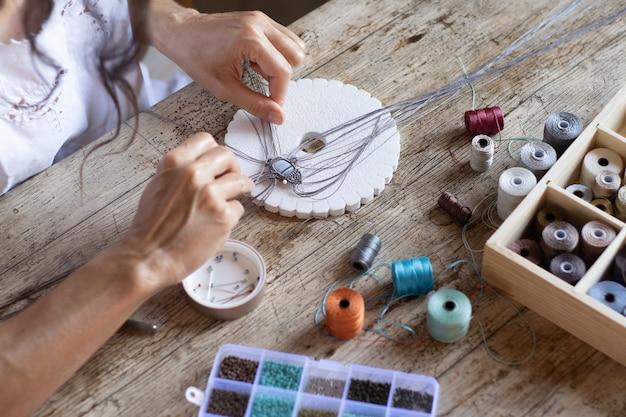 Bovenaanzicht van een vrouw die vanuit huis werkt en handgemaakt micro-macrame-juweel maakt met gekleurde klosjes draad