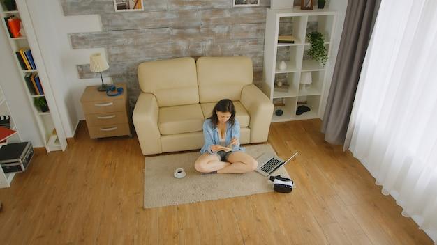 Bovenaanzicht van een vrouw in korte spijkerbroek die een boek op de vloer leest met een kopje koffie naast haar