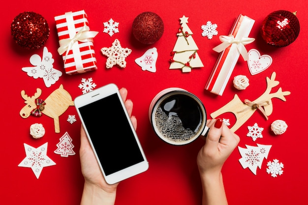 Bovenaanzicht van een vrouw met een telefoon in de ene hand en een kopje koffie in een andere hand op rood