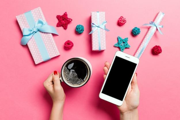 Bovenaanzicht van een vrouw met een telefoon in de ene hand en een kopje koffie in een andere hand op roze achtergrond. kerstdecoraties en speelgoed. nieuwjaar vakantie concept. mockup