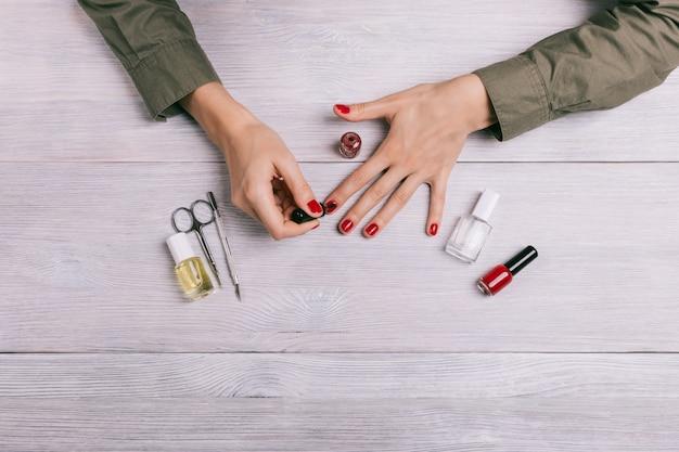 Bovenaanzicht van een vrouw schildert haar nagels met rode lak