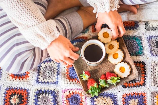 Bovenaanzicht van een vrouw thuis die 's ochtends ontbijt op het bed doet met koffie en koekjes en aardbei
