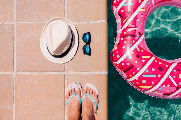 Bovenaanzicht van een vrouw voeten plat lag met hoed en zonnebril vrouw ontspannen in het zwembad met roze donuts in warme zonnige dag zomervakantie idyllische vakantie concept