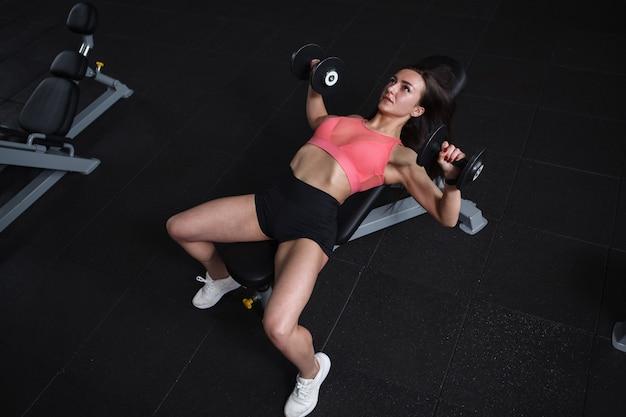 Bovenaanzicht van een vrouwelijke atleet die bankdrukken doet met gewichten