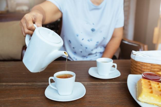 Bovenaanzicht van een vrouwelijke gieten thee op houten tafel