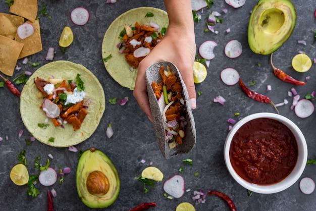 Bovenaanzicht van een vrouwelijke hand met een taco met vlees en groenten