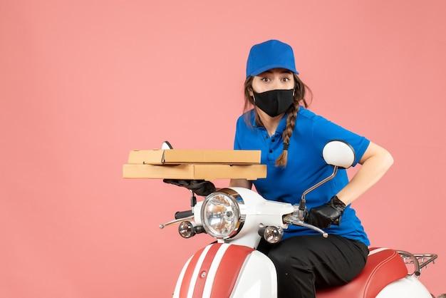 Bovenaanzicht van een vrouwelijke koerier met een medisch masker en handschoenen die op een scooter zit en bestellingen aflevert op pastel perzik