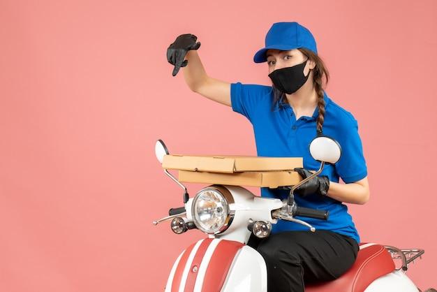 Bovenaanzicht van een vrouwelijke koerier met een medisch masker en handschoenen die op een scooter zitten en bestellingen afleveren die naar beneden wijzen op een pastelkleurige perzikachtergrond