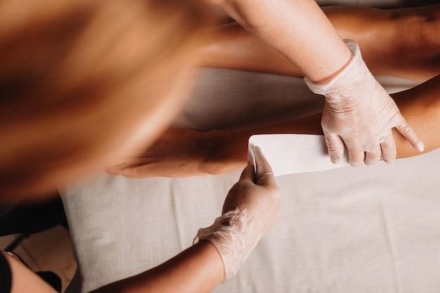 Bovenaanzicht van een waxprocedure die wordt uitgevoerd door een ervaren spa-medewerker terwijl de cliënt ligt