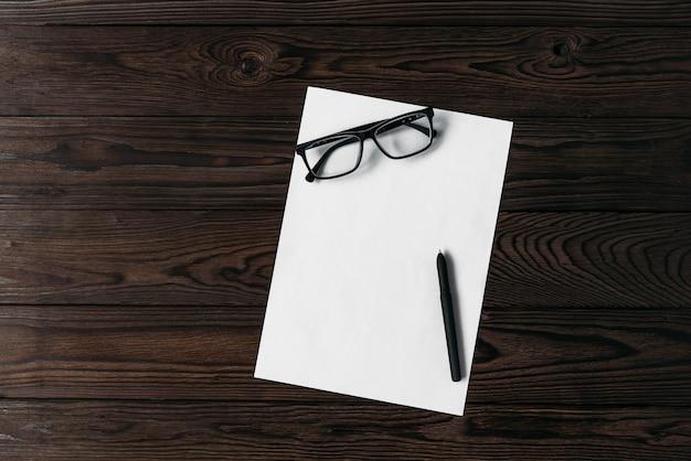 Bovenaanzicht van een wit blanco vel papier met een pen en glazen op een houten tafel.