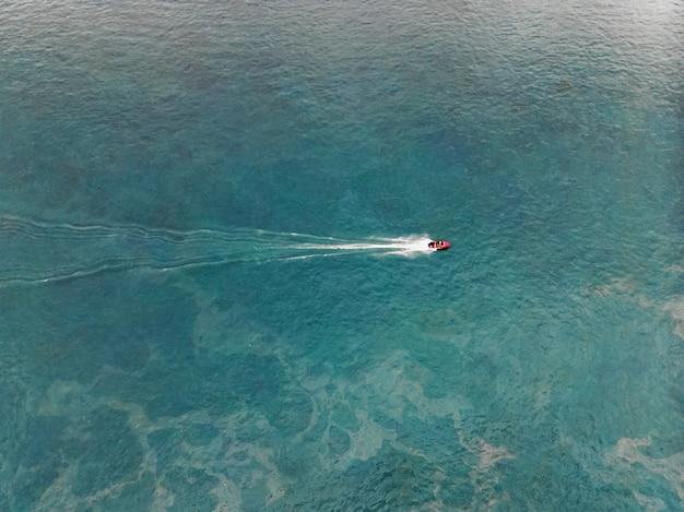 Bovenaanzicht van een witte boot die in de blauwe zee vaart.