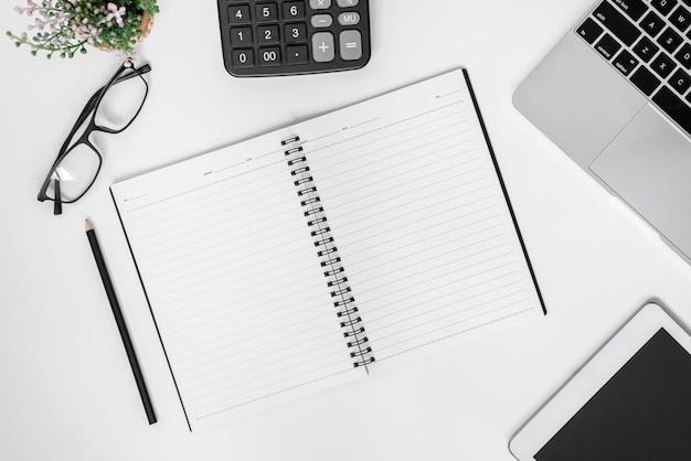 Bovenaanzicht van een witte bureautafel met veel dingen erop. computertoetsenbord en andere kantoorbenodigdheden.