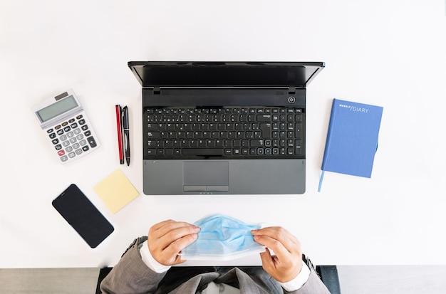 Bovenaanzicht van een witte kantoortafel met een laptop, rekenmachine, mobiele telefoon, post-it, pennen, notitieboekje en met een bedrijfsmedewerker die een gezichtsmasker draagt vanwege de coronaviruspandemie covid19