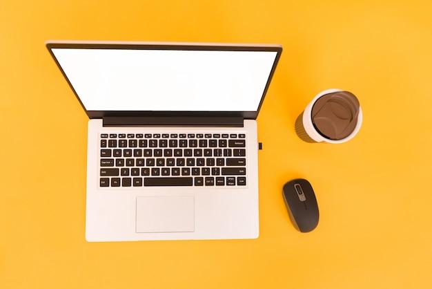Bovenaanzicht van een zakelijke werkplek met laptop op een gele achtergrond.
