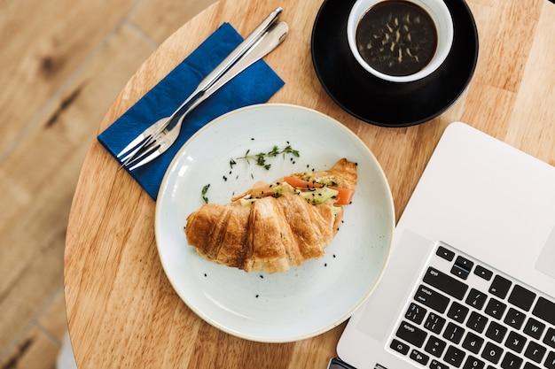 Bovenaanzicht van een zakenlunch met croissant en koffiekopje over ronde tafel met laptopcomputer
