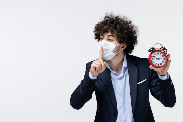 Bovenaanzicht van een zakenman in pak en zijn masker dragend met een klok die een stiltegebaar maakt