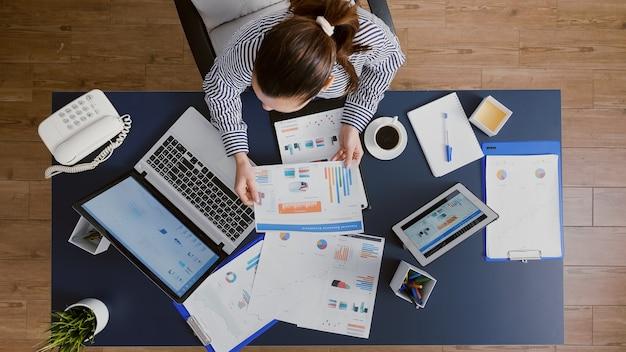 Bovenaanzicht van een zakenvrouw die aan een bureautafel zit en financiële boekhoudkundige documenten controleert