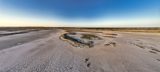 Bovenaanzicht van een zanderig moeras met grote stukken gras en struiken