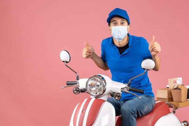Bovenaanzicht van een zelfverzekerde bezorger met een medisch masker met een hoed die op een scooter zit en een goed gebaar maakt op een pastelkleurige perzikachtergrond