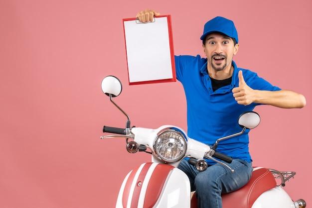 Bovenaanzicht van een zelfverzekerde koeriersman met een hoed die op een scooter zit en een document toont dat een goed gebaar maakt op een pastelkleurige perzikachtergrond
