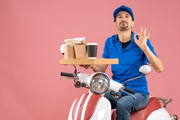 Bovenaanzicht van een zelfverzekerde koeriersman met een hoed die op een scooter zit en een perfect gebaar maakt op een pastelkleurige perzikachtergrond
