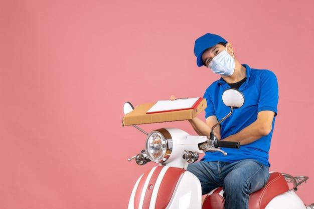 Bovenaanzicht van een zelfverzekerde mannelijke bezorger met een masker met een hoed die op een scooter zit en bestellingen aflevert met een document op een perzikachtergrond