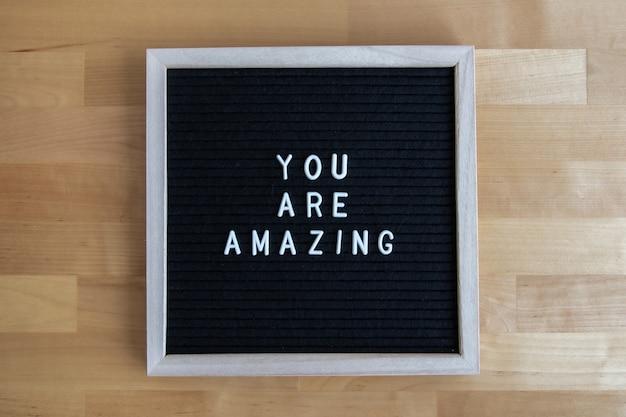 Bovenaanzicht van een zwart leeg bord op een houten tafel met jou is geweldig