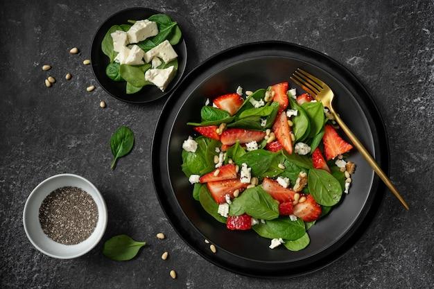 Bovenaanzicht van een zwarte plaat met aardbei spinazie salade en de ingrediënten