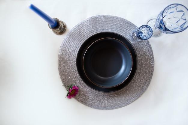 Bovenaanzicht van een zwarte plaat met blauwe glazen en kaarsen.