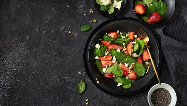 Bovenaanzicht van een zwarte plaat van aardbeien spinazie salade en de ingrediënten