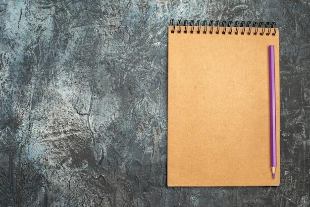 Bovenaanzicht van eenvoudige kladblok met potlood op grijze ondergrond